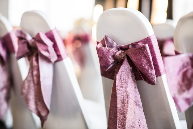 Cadeira branca com laço rosa para a cerimônia
