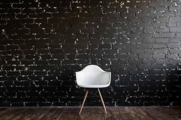 Cadeira branca em pé na sala no piso de madeira marrom sobre parede de tijolo preto