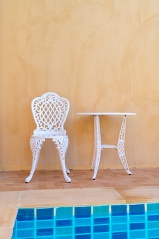 Cadeira branca vazia e mesa ao lado da piscina