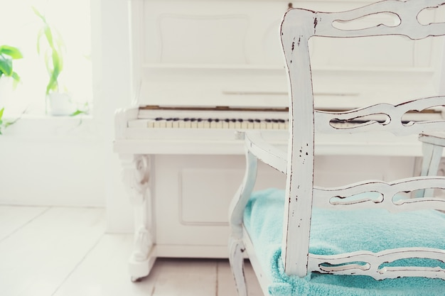 Cadeira branca vintage e piano em uma sala branca