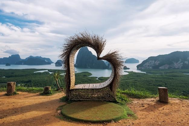 Cadeira com coração de madeira para ver os cársticos de calcário da baía de phang nga em samed nangshee, tailândia