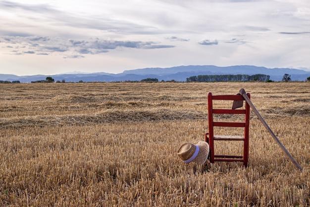 Cadeira com enxada e chapéu no meio de um campo de cereais, conceito de agricultura local