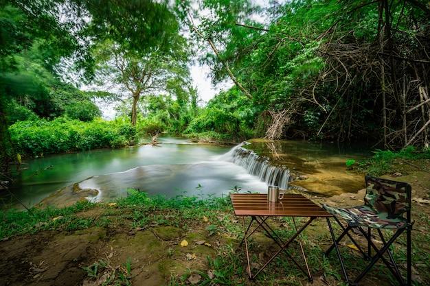 Cadeira de acampamento com mesa em frente a cachoeira de férias