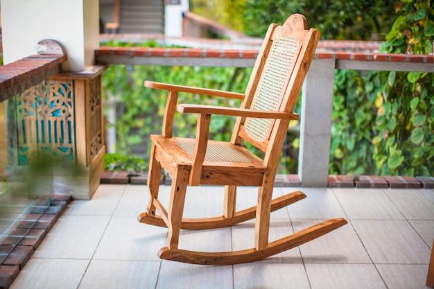 Cadeira de balanço de madeira no terraço de um hotel exótico