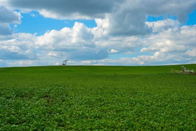 Cadeira de balanço de óleo moderna em um campo de grama verde.