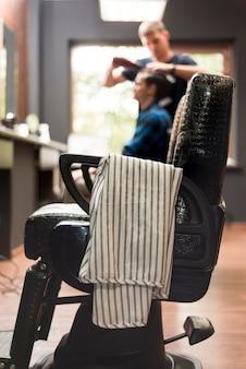 Cadeira de barbearia com homem desfocado no fundo