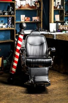 Cadeira de barbeiro vintage elegante. logotipo da barbearia, símbolo. poste de barbearia. cabeleireiro no interior da barbearia. cadeira de barbearia. poltrona de barbearia, salão, barbearia para homens.