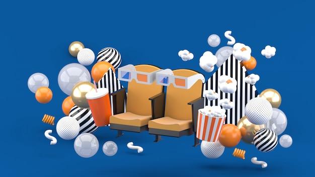 Cadeira de cinema refrigerantes e pipoca entre as bolas coloridas no azul. renderização em 3d.