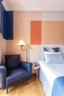 Cadeira de couro macio no quarto para descanso, com travesseiros e cama