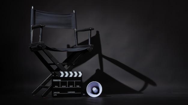 Cadeira de diretor preta e claquete ou claquete de cinema com megafone em fundo preto. use na produção de vídeo ou na indústria de cinema cinematográfica