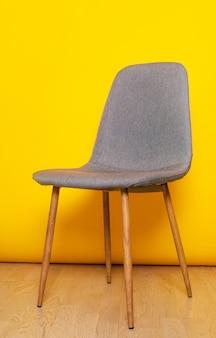 Cadeira de escritório cinza isolada no fundo da parede amarela Foto Premium