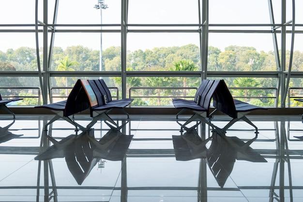 Cadeira de filas com janela de vidro no terminal portão