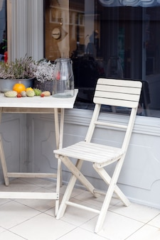 Cadeira de jardim de madeira branca e mesa com lindas flores perto da casa de entrada