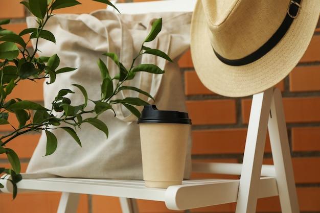 Cadeira de madeira com chapéu, copo de papel e bolsa de algodão no fundo da parede de tijolos