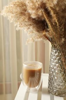 Cadeira de madeira com vaso de flores do campo e copo de latte