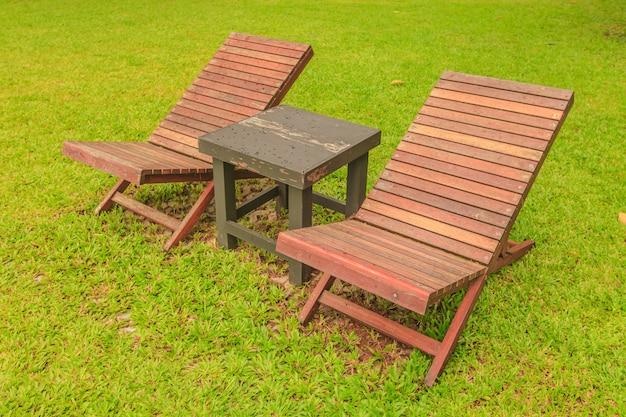 Cadeira de madeira do sol no quintal verde