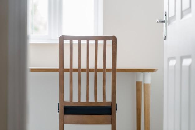 Cadeira de madeira e uma mesa em uma sala branca e tranquila, disparada por uma abertura de porta