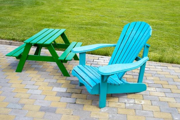 Cadeira de madeira e uma mesa perto do gramado