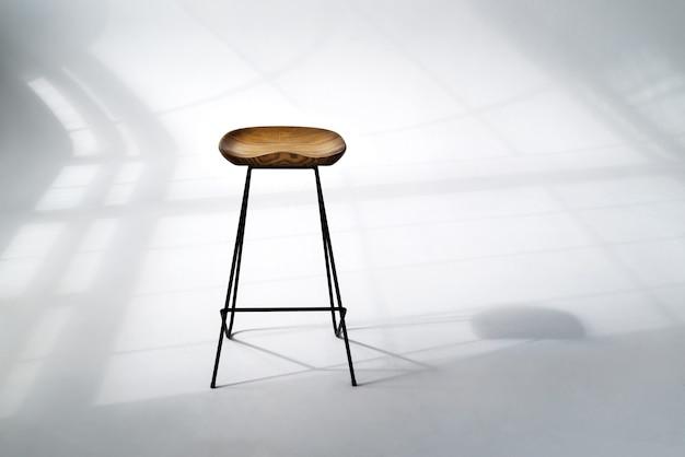 Cadeira de madeira em pé no quarto do meio com sombras rígidas de moldura de janela no piso branco