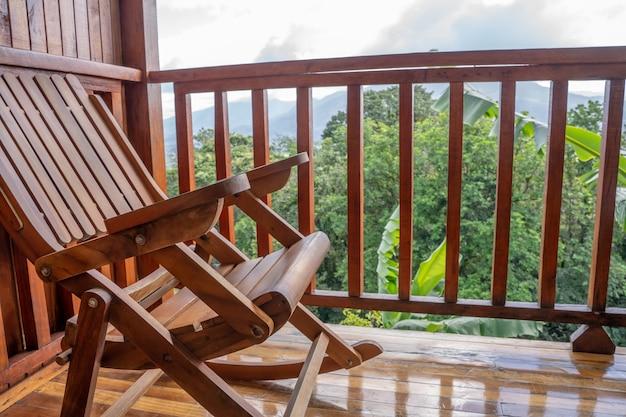 Cadeira de madeira em um terraço de madeira de um hotel com vista para a selva e um vulcão ao fundo