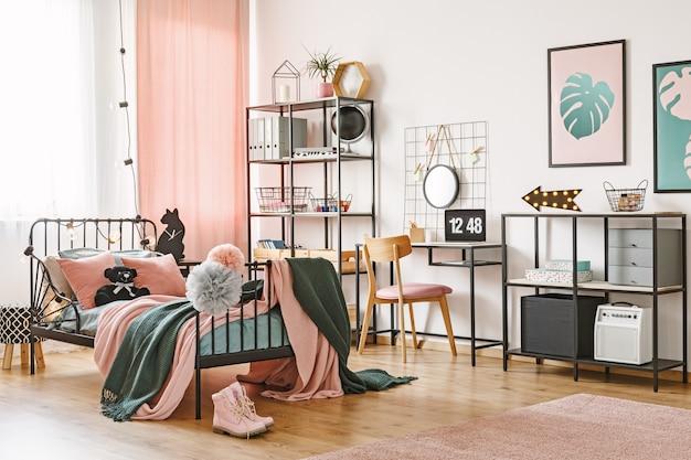 Cadeira de madeira na mesa com laptop no interior do quarto feminino com roupa de cama rosa e verde