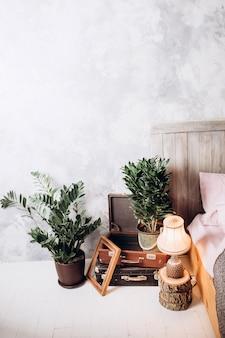 Cadeira de madeira na penteadeira no interior do quarto pastel rosa com lâmpada de ouro ao lado da cama