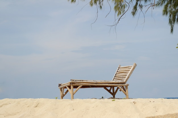 Cadeira de madeira na praia de areia para o conceito de verão