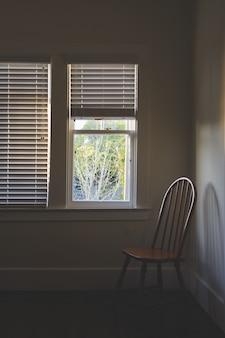 Cadeira de madeira perto da janela com persianas