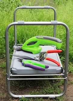 Cadeira de mesa dobrável na qual ferramentas de jardim para poda de plantas e árvores