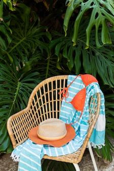 Cadeira de palha e arranjo de chapéu
