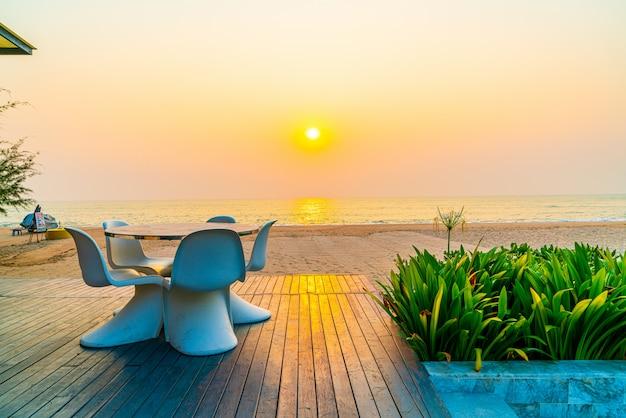 Cadeira de pátio ao ar livre vazia e mesa com praia do mar