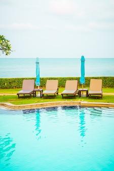 Cadeira de piscina com guarda-sol ao redor da piscina