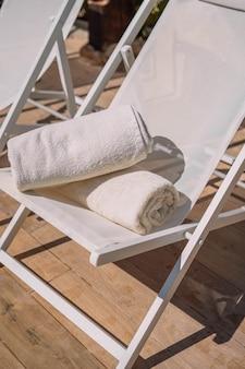 Cadeira de piscina com toalhas dobradas