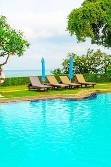 Cadeira de piscina e guarda-sol ao redor da piscina com fundo do mar