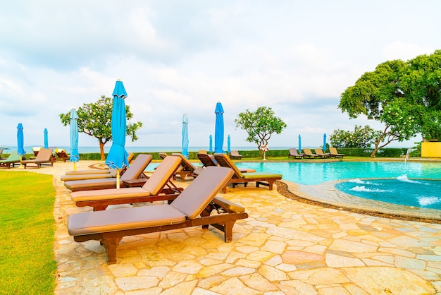 Cadeira de piscina e guarda-sol ao redor da piscina com superfície do oceano