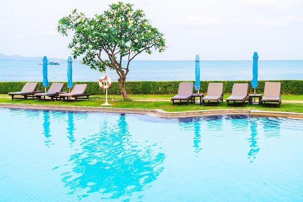 Cadeira de piscina ou piscina com cama com guarda-chuva ao redor da piscina