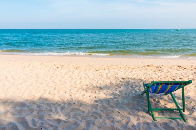 Cadeira de praia de madeira vazia no fundo da praia