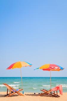 Cadeira de praia e guarda-chuva na praia de areia