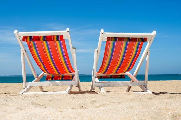 Cadeira de praia em uma praia tropical com lindas águas turquesa do oceano, areia branca e céu azul, horário de verão