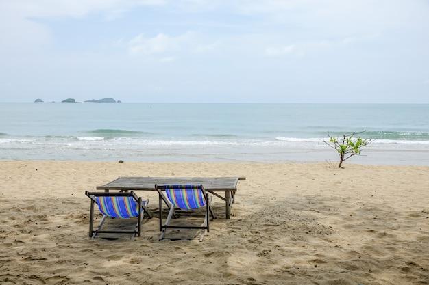 Cadeira de praia na areia branca com onda do mar e ensolarada.