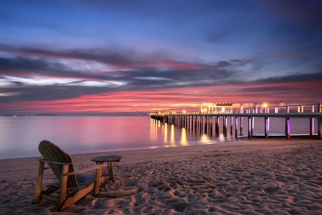Cadeira de praia na praia, ponte de madeira para o mar.