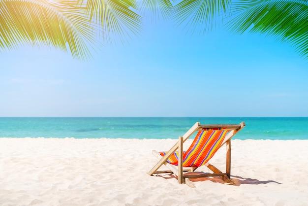 Cadeira de praia na praia tropical em tailândia com o céu azul no dia ensolarado.