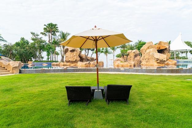 Cadeira de praia vazia com guarda-chuva ao redor da piscina