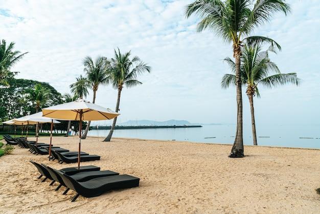 Cadeira de praia vazia com palmeira na praia com fundo do mar