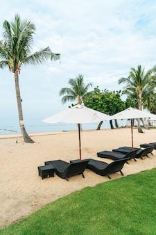 Cadeira de praia vazia com palmeira na praia com vista para o mar