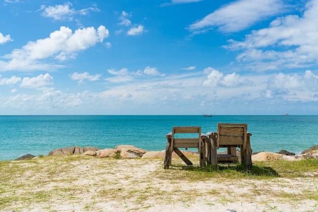 Cadeira de praia vazia com vista sobre o céu azul claro e oceano