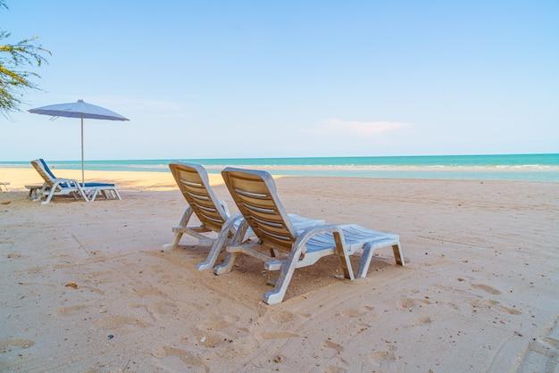 Cadeira de praia vazia na areia com o mar do oceano