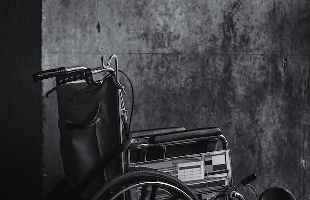 Cadeira de rodas dobrada ao lado da parede. tristes notícias para o conceito de hospital. depressão com o envelhecimento da sociedade. cadeira de rodas vazia e solitária. equipamento médico para atendimento a pacientes e assistentes idosos com deficiência