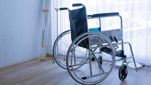 Cadeira de rodas moderna vazia e bengala ou bengalas no quarto de hospital.