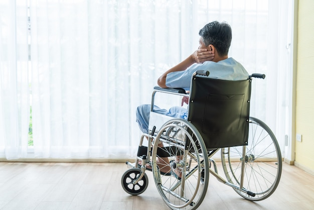 Cadeira de rodas paciente asiática no quarto vazio